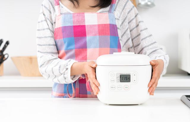 炊飯器を抱える主婦